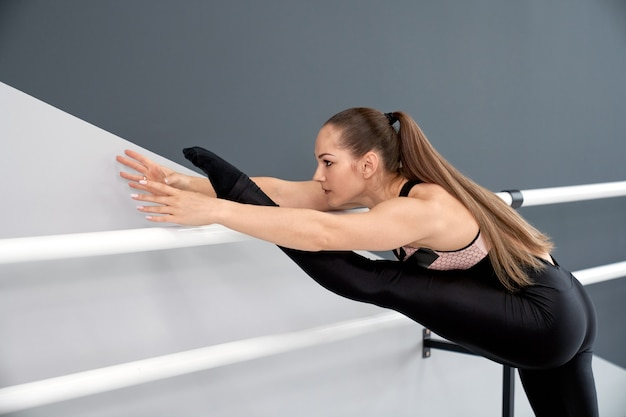 Woman stretching using handrails in hall