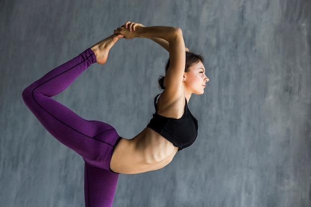 Woman stretching while holding her foot
