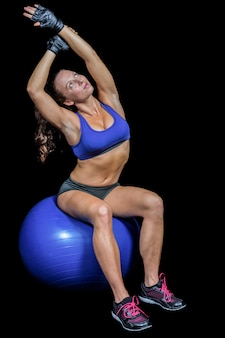 Woman stretching while sitting on exercise ball against black background