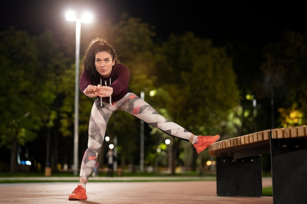 Woman stretching with bench full shot