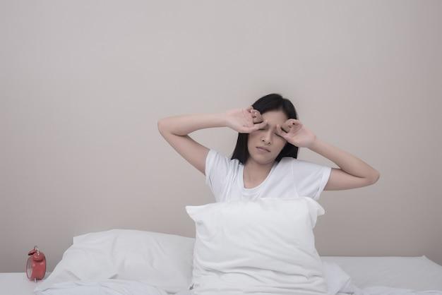 女、伸びる、目を閉じて、ベッドに座っている