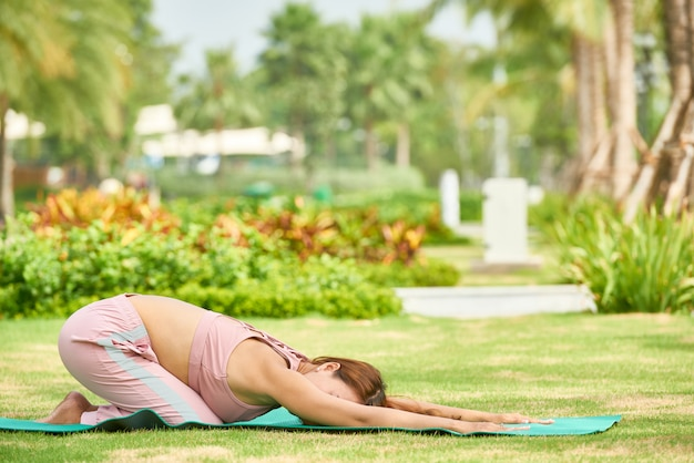 Woman in stretching yoga asana outdoors