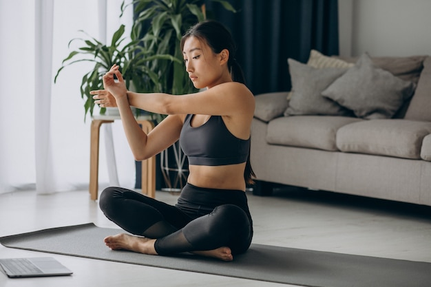 Woman stretching on yoga mat at home