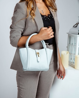 Woman in striped blazer and trousers holding small blue bag