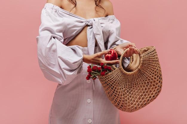 Donna in camicetta e gonna moderne a righe con bottone bianco che posa mela rossa in una graziosa borsetta di paglia con bellissimi fiori
