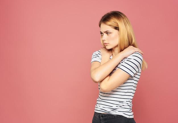 여자 스트라이프 t- 셔츠 금발 모델 분홍색 배경 초상화 클로즈업 감정. 고품질 사진