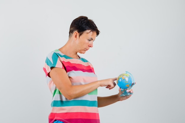 Woman in striped t-shirt choosing destination on globe model and looking focused