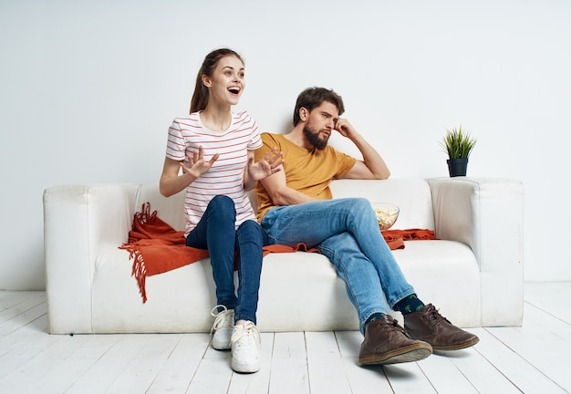 A woman in a striped t-shirt and a man on the couch watching the tv in a bright room