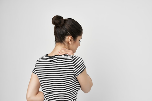 Woman in a striped t-shirt pain in the neck health problems. high quality photo