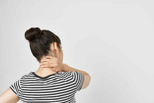 Woman in striped tshirt back pain discomfort discontent back view