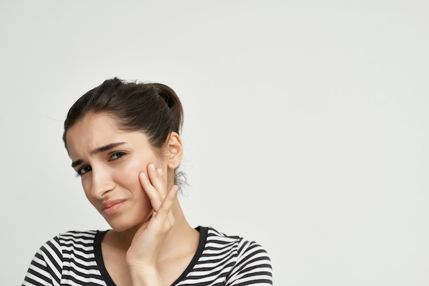 Woman in striped tshirt holds face pain in teeth dentist treatment