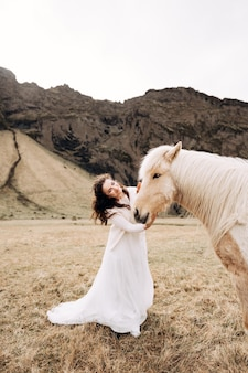 女性は黄色い草のフィールドで豪華なたてがみで馬の顔を撫でる