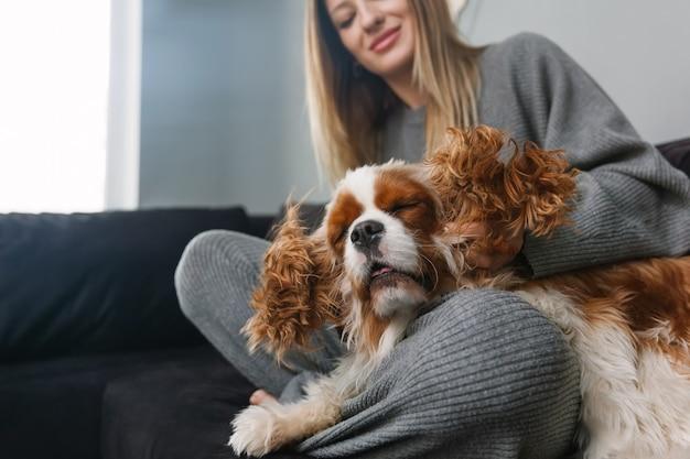 Женщина гладит свою собаку спаниеля