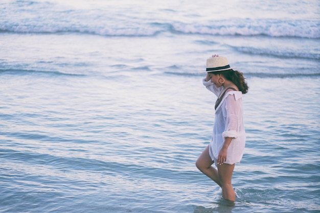 A woman strolling on the beach with the sea and blue sky background
