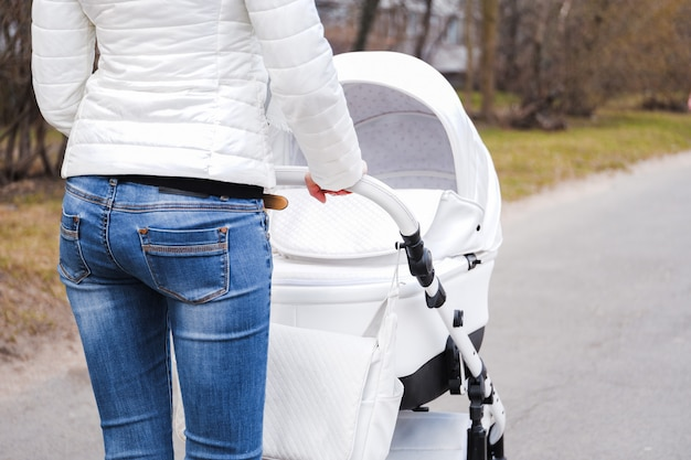 Woman strolling with baby carriage rear view