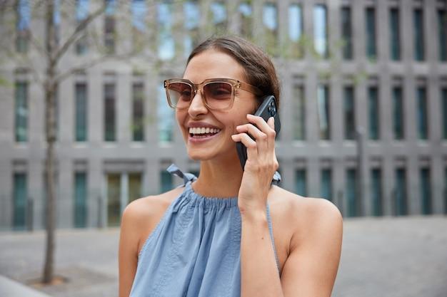 휴대 전화를 통해 현대 도시 회담의 거리를 산책하는 여성은 트렌디 한 선글라스를 착용하고 파란 드레스 미소는 긍정적 인 대화 중에 로밍 연결 웃음을 광범위하게 사용합니다