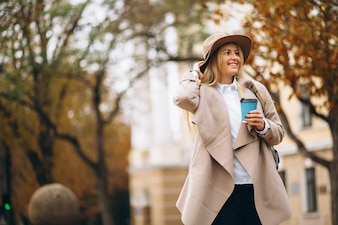 Woman student in hat drinking coffee
