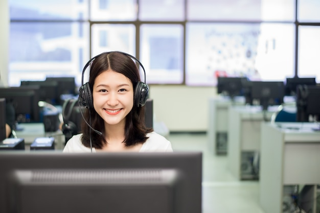 Woman student posing with a computer while studying in it room.