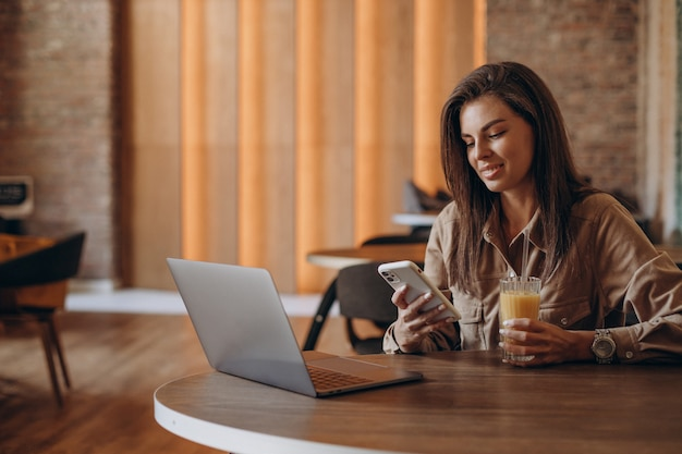 Woman student studying on laptop in a cafe