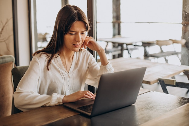 Woman student studying online in a cafe