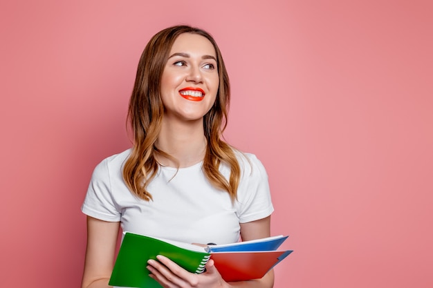 Woman student wearing white t-shirt smiling and holding notepad isolated on pink background