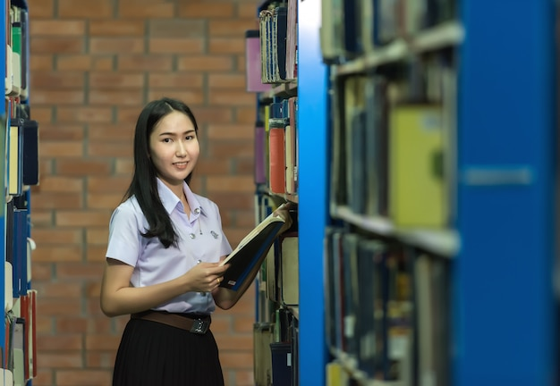Woman students are a handful of books the bookshelf in the library
