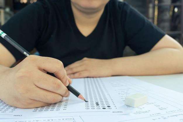 解答用紙と数学の質問シートに選択した選択肢を鉛筆で書く女性学生の手。試験を行う学生。学校の試験