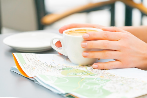 Woman study map drinking coffee in a street cafe. redhead happy girl travel canary islands and looking for a new place to visit. sunny day.
