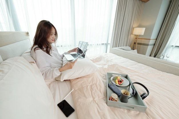 Woman studying in bed
