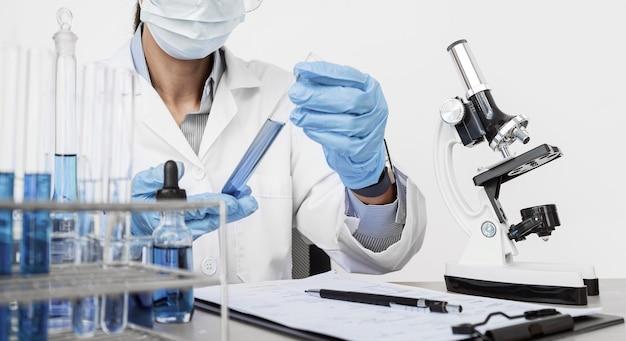 Donna che studia gli elementi chimici mentre indossa una maschera facciale