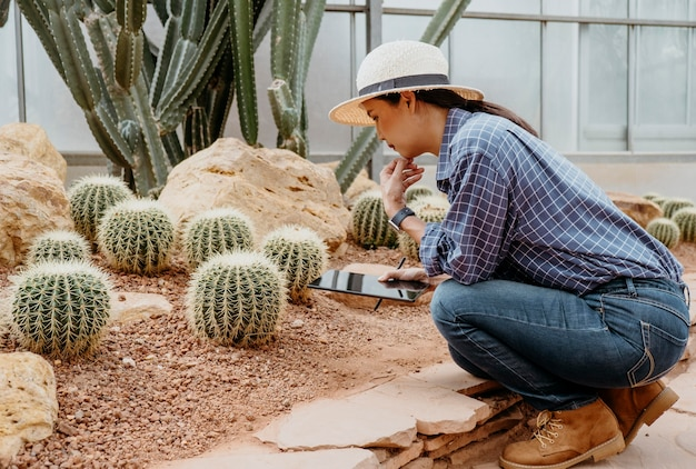 Woman studying different plants with a tablet