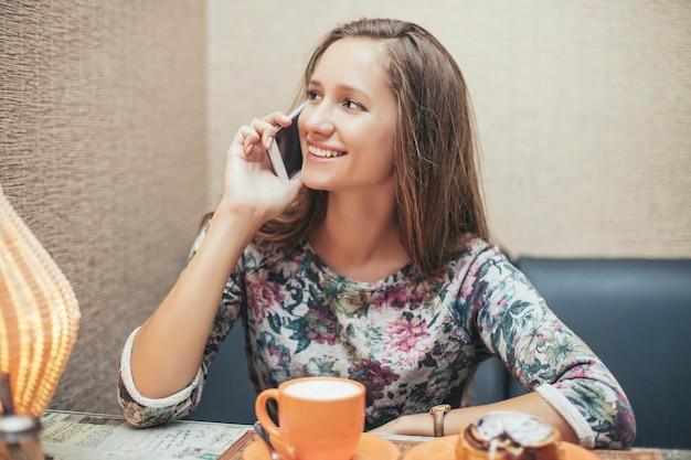 ペストリーと電話でコーヒーショップの女性スタイルの美しいモデル