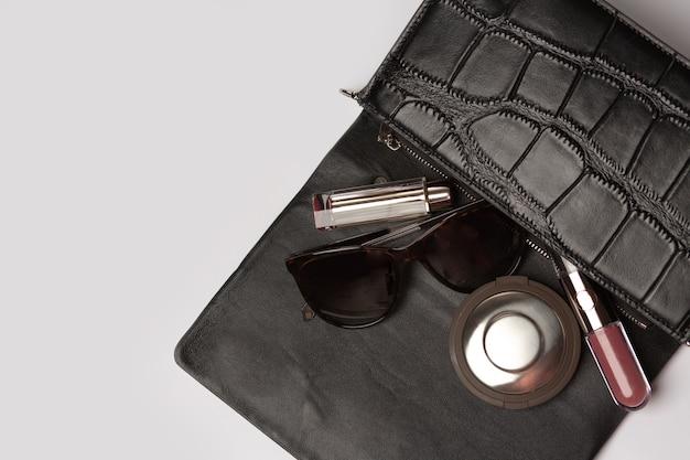 女性スタイルのコンセプト:灰色の背景の上に蛍光ペン、口紅、眼鏡をドロップアウトした革のバッグ。テキスト用のスペース