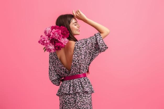 Stile di donna in abito con fiori su sfondo rosa