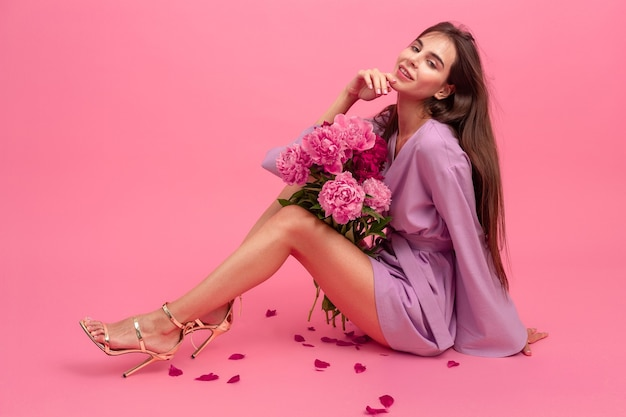 Woman style in dress with flowers on pink background