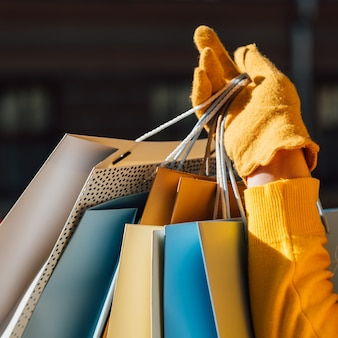 Woman style and fashion closeup of lady hand in glove holding bunch of shopping bags