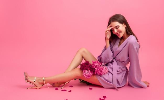 Женский стиль в платье с цветами на розовом фоне
