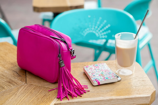 Woman stylish accessories on table in cafe