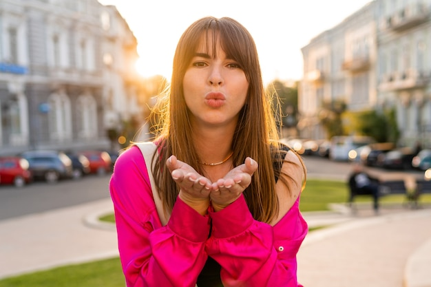 Woman in stylish casual outfit sending kiss, posing in old european city.