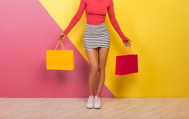 Woman in stylish colorful outfit holding shopping bags in hands