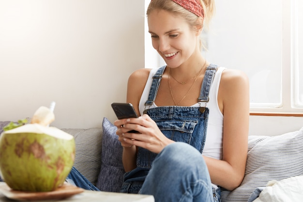 Woman in stylish denim overalls in coffee shop