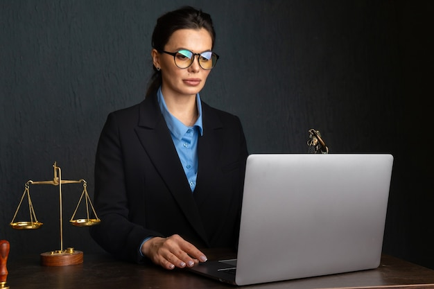 Woman in stylish glasses writing notary in textbook during online learning on laptop computer, sitting in restaurant interior. female marketing coordinator using diary for work