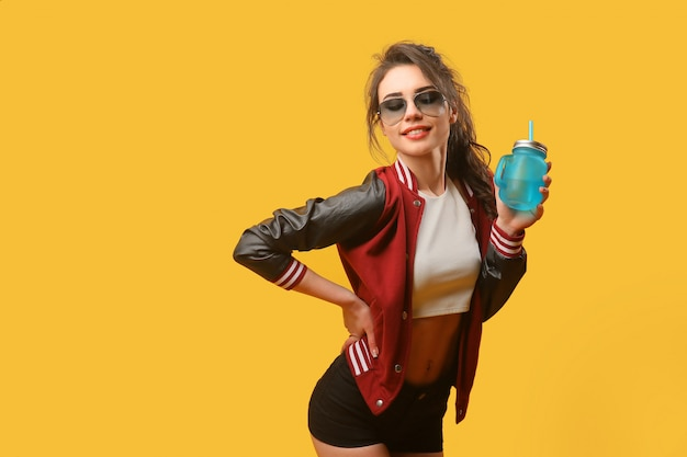 Woman in stylish jacket with drinking jar