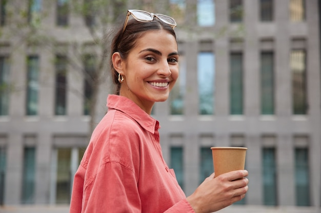 Woman in stylish red shirt sunglasses on head strolls in unknown city drinks coffee from paper cup enjoys leisure time smiles broadly poses against blurred building
