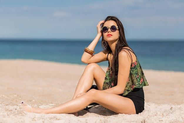 Donna in elegante autfit tropicale in posa sulla spiaggia.
