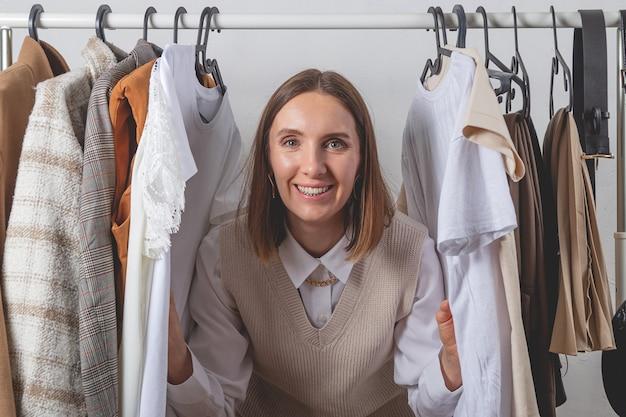 Стилист женщина среди одежды на стильных перилах в гардеробной