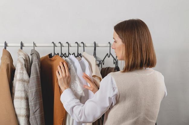 Стилист выбирает одежду на стильных перилах в гардеробной
