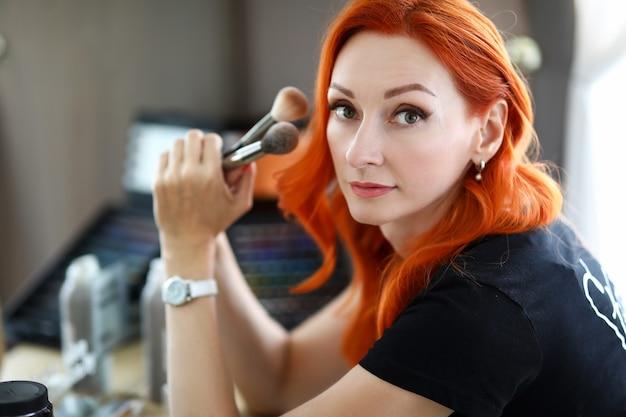 女性スタイリストがプロのメイクブラシを持って美容院のマスターが職場に座って