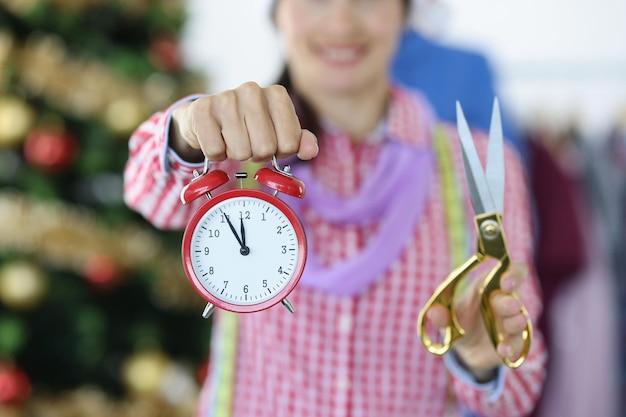 여자 스타일리스트는 저녁 크리스마스 트리 바느질을 배경으로 빨간색 알람 시계와 가위를 들고 있다