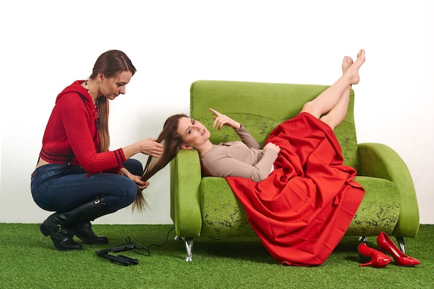 Woman stylist straightens the hairstyle of the model while she is resting in a break between shoots, lying on the couch in the studio